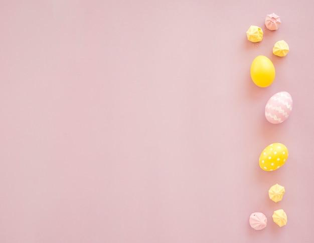 Coloridos huevos de pascua con dulces en mesa