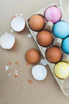 Coloridos huevos de pascua en estante con cáscara