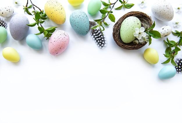 Coloridos huevos de pascua con flores de primavera sobre fondo blanco.