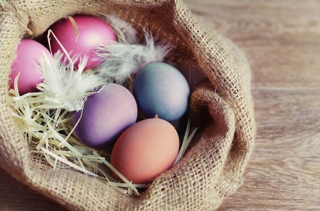 Coloridos huevos de pascua en mesa de madera.