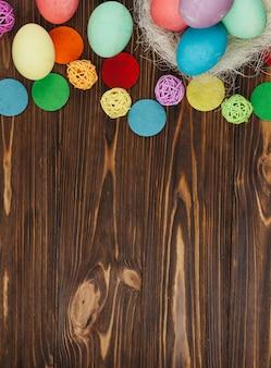 Coloridos huevos de pascua en nido en mesa