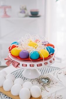 Coloridos huevos de pascua con papel triturado sobre la mesa blanca