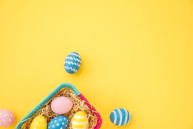 Coloridos huevos de pascua en una pequeña cesta en mesa amarilla