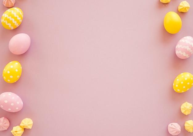 Coloridos huevos de pascua con pequeños dulces en mesa