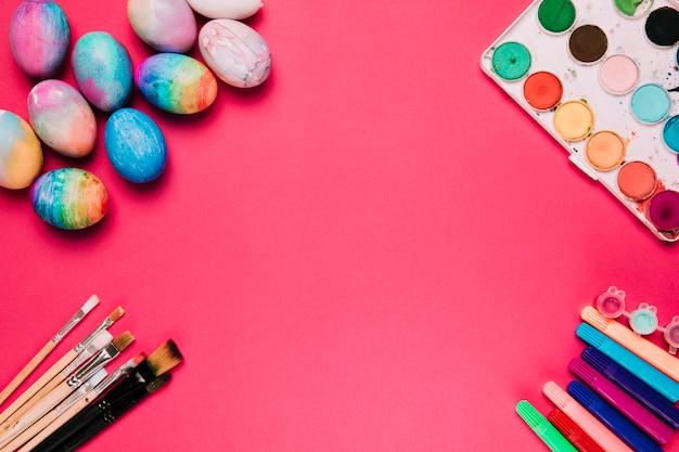 Coloridos huevos de pascua pintados; pinceles; caja de pintura y rotulador sobre fondo rosa.