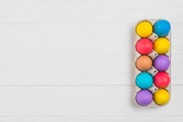 Coloridos huevos de pascua en rejilla en mesa de madera