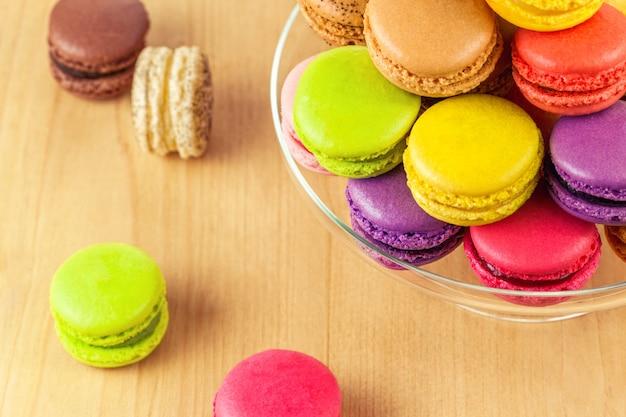 Coloridos macarons franceses en un soporte de pastel de vidrio