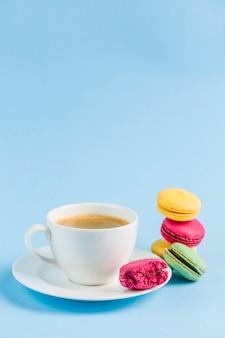 Coloridos macarrones con una blanca taza de café en un copyspace azul, primer plano, flatley con copyspace