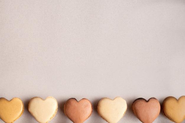 Coloridos macarrones en forma de corazón en una fila en color beige