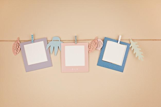 Con coloridos marcos de fotos colgando de la cuerda con espacio para copiar texto y fotos