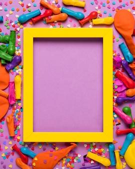 Coloridos objetos festivos con marco vacío amarillo