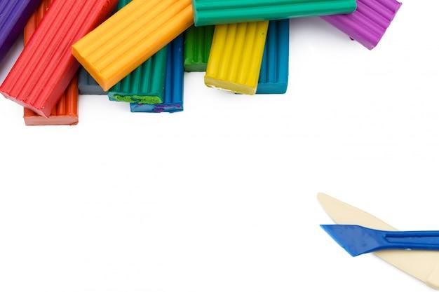 Coloridos palos de plastilina sobre superficie blanca