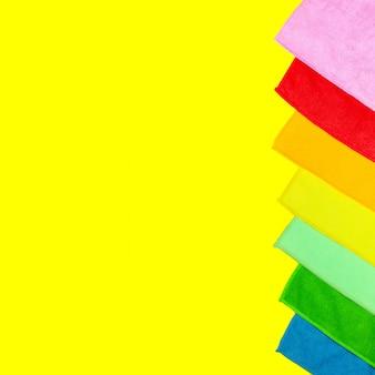 Coloridos paños de microfibra en polvo se encuentran en un amarillo brillante