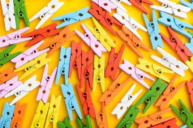 Coloridos pasadores de madera pequeños sobre papel naranja