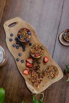 Coloridos postres dulces de desayuno saludable algunos diferentes budines de chia en frascos de vidrio sobre la mesa de madera en la cocina de casa.