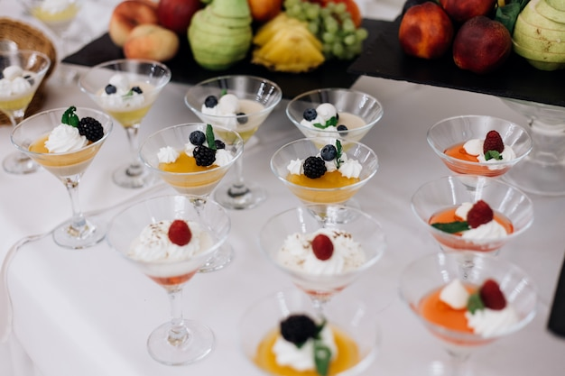 Coloridos postres de gelatina con bayas y crema en la cristalería en el buffet del banquete