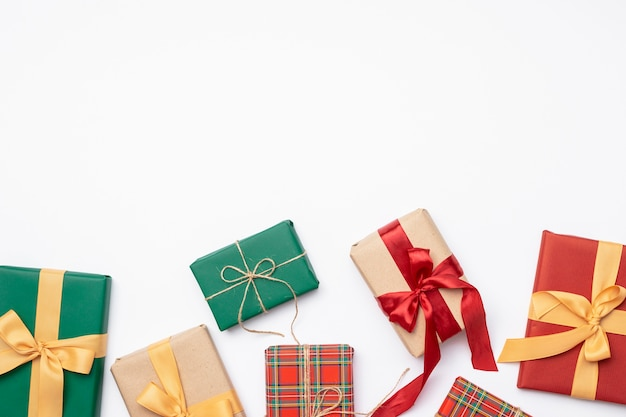 Coloridos regalos de navidad con cinta sobre fondo blanco.