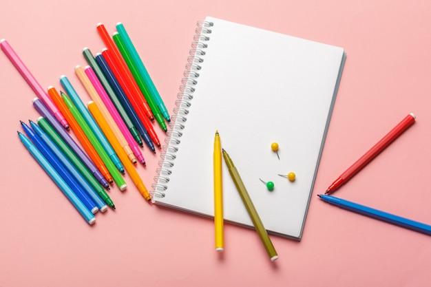 Coloridos rotuladores con papel de bloc de notas en blanco sobre fondo rosa pastel