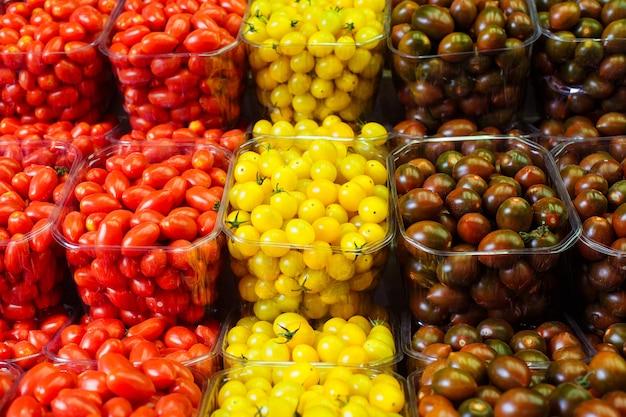 Coloridos tomates cherry en cestas de plástico