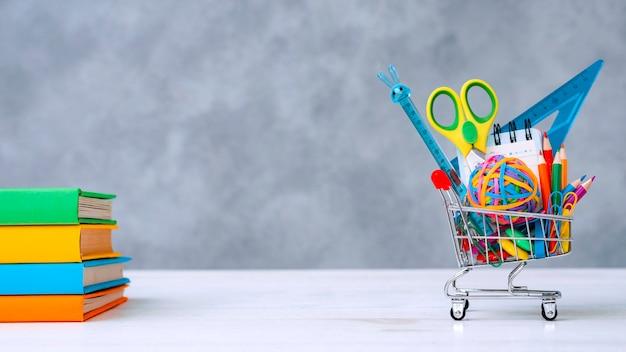 Coloridos útiles escolares canasta de compras gris con un espacio de texto copia.