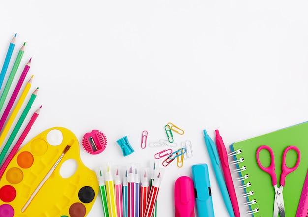 Coloridos útiles escolares y papelería sobre fondo blanco. copia espacio, vista superior. concepto de regreso a la escuela.