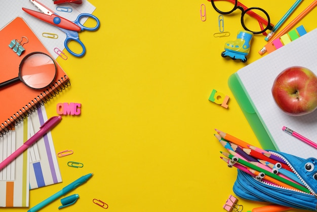 Coloridos útiles de oficina y estudiantes en amarillo
