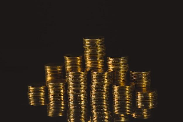 Columnas crecientes de monedas, paso de pilas de monedas sobre fondo oscuro
