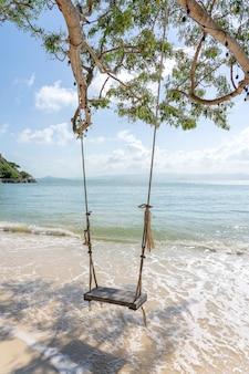 Columpio colgar de un árbol tropical sobre el mar de playa de arena de verano en la isla de koh phangan, tailandia. concepto de verano, viajes, vacaciones y vacaciones.