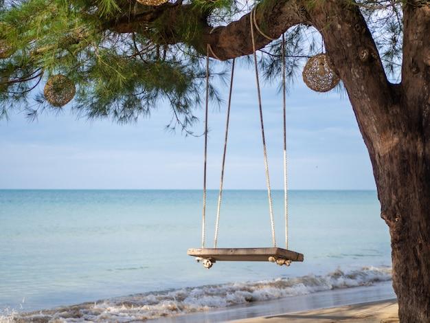 Columpio de madera colgando del árbol en el fondo hay un mar azul.