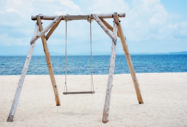 Columpio de madera en la playa y paisaje marino marino de agua de mar azul océano