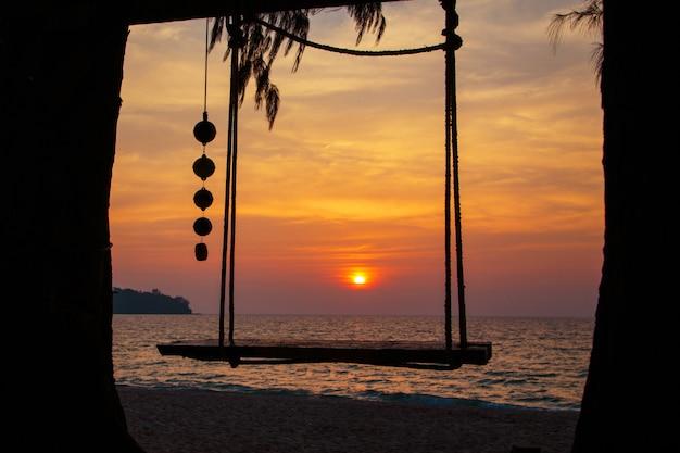 Columpio de madera puesta de sol en la playa del mar