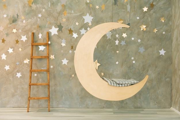 Columpio suspendido en forma de luna con estrellas.