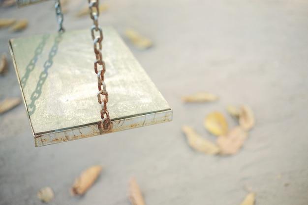 Columpios de cadena colgando en el jardín, suave imagen en tonos vintage.