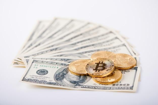 Comaprison dinero. bitcoins dorados como innovador dinero virtual futurista y billetes de cien dólares como forma antigua de dinero.