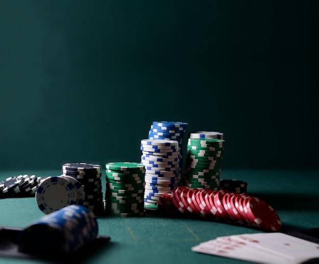 Combinación de fichas de casino y cartas de escalera real en la mesa verde. tema del juego de póquer