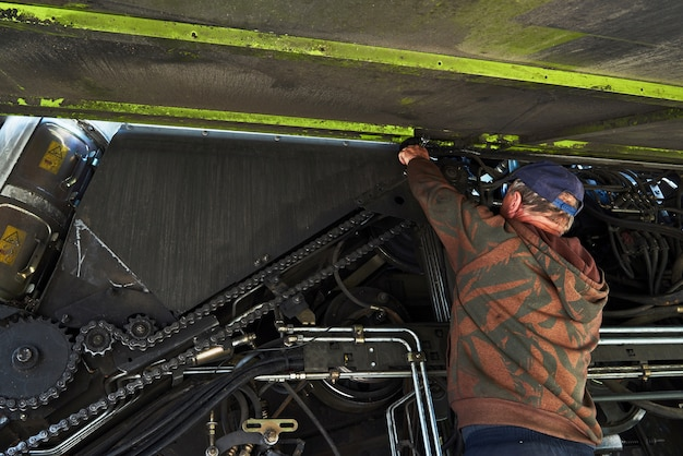 Combine el servicio de la máquina, el mecánico repara el motor al aire libre.