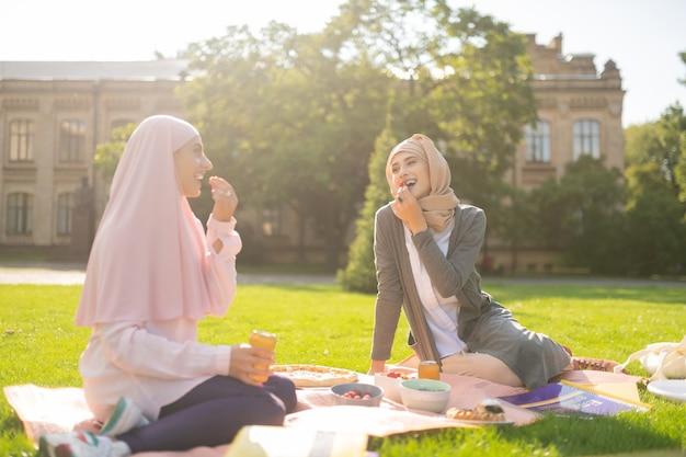 Comer deliciosas bayas. estudiante musulmán sonriente almorzando fuera comiendo deliciosas bayas