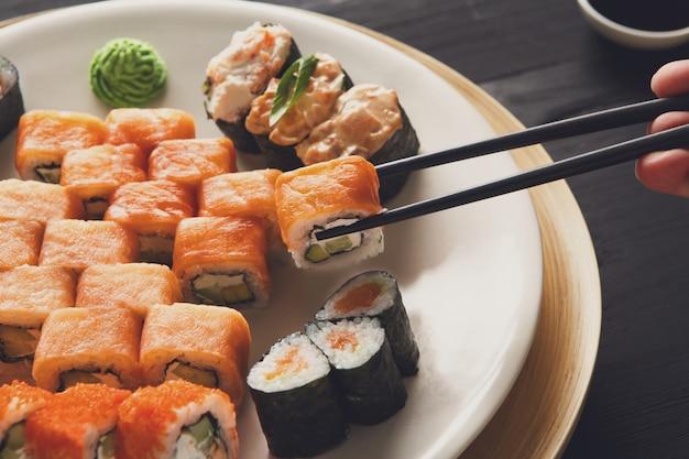 Comer rollos de sushi en un restaurante de comida japonesa