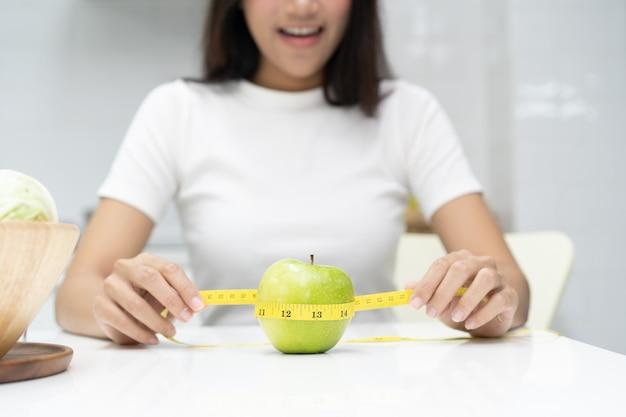 Comer sano y concepto de dieta. cinta de la medida del uso de la muchacha que mide la manzana verde en la tabla.