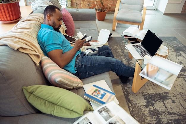 Comer, ver cine, parece muy aburrido. hombre afroamericano que se queda en casa durante la cuarentena debido a la propagación del coronavirus, covid-19. tratando de divertirme. concepto de salud y medicina.