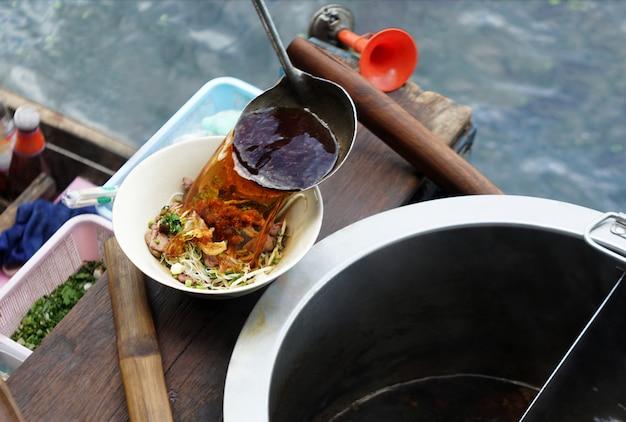 Comerciante cocinero vertiendo sopa de calor a base de hierbas en un tazón blanco de fideos estilo tailandés en barco de madera flotante en el río