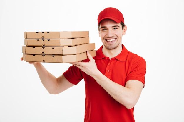 Comerciante complacido con camiseta roja y gorra trabajando en el servicio de entrega y sosteniendo una pila de cajas de pizza, aislado sobre un espacio en blanco