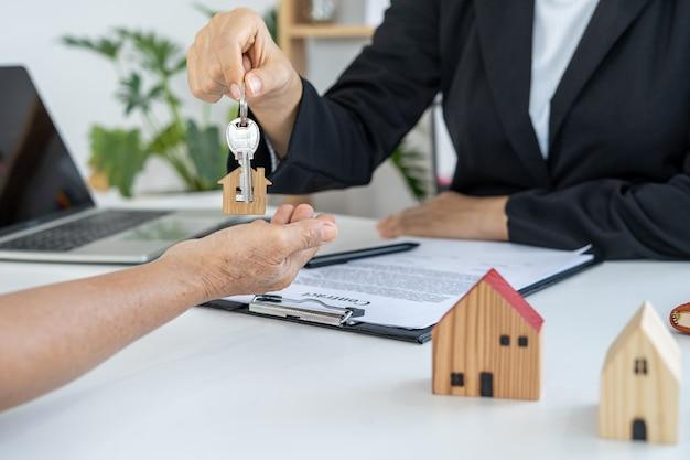 El comerciante envía la llave de la casa al nuevo propietario después de aceptar el contrato de compraventa de la casa. alquilar casa y comprar concepto.