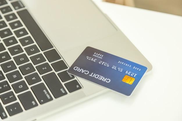 Comercio electrónico, compras en línea y concepto de tecnología. ciérrese para arriba de la tarjeta de crédito falsa falsa en el ordenador portátil en el escritorio blanco.