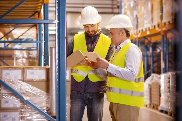 Comercio a gran escala. encantado de buen hombre agujereando una caja mientras está de pie con su colega en el almacén