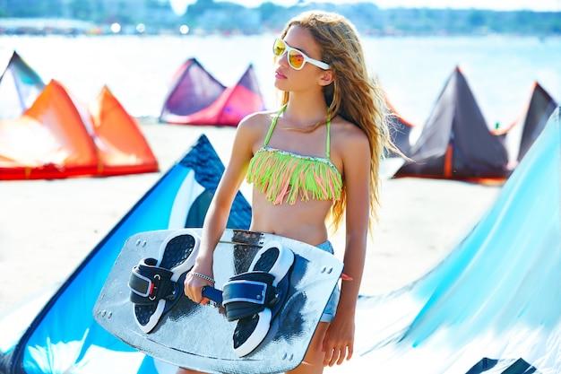 Cometa rubia surf chica adolescente en la playa de verano