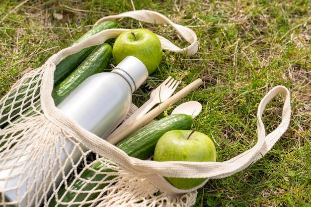 Comida de alto ángulo en bolsa reutilizable sobre hierba