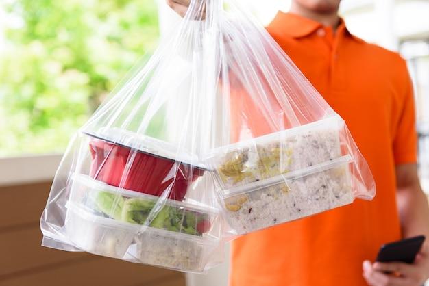 Comida asiática en cajas para llevar entregadas al cliente en casa por un repartidor en uniforme naranja