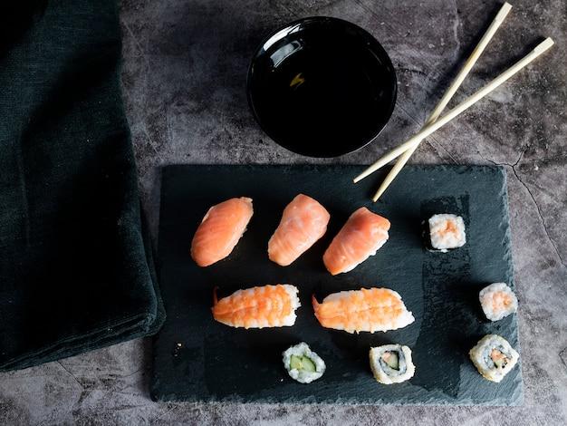Comida asiática en el espacio negro, sushi, salmón, soja, palillos, plato