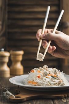 Comida asiática fideos funchoza con pollo y palos para comida en madera con copyspace